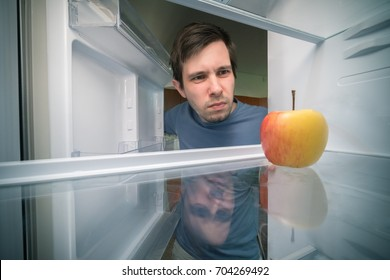 Hungry man is looking for food in fridge. Only apple is inside empty fridge.