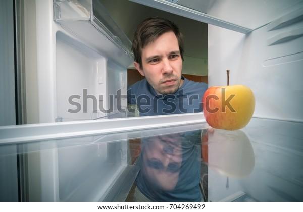 Der Hungrige sucht im Kühlschrank Essen. Nur Apfel ist im leeren Kühlschrank.