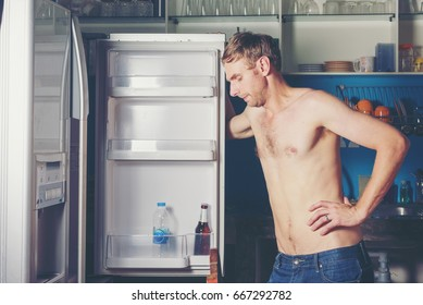 Hungry man opening and looking for food in refrigerator,at the empty refrigerator