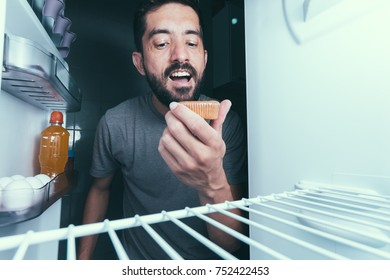 Hungry man opens the refrigerator at night