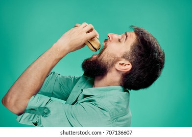 Hungry man in profile eating cheeseburger on green background