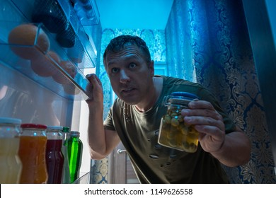 Hungry man searching in his fridge at night for a snack holding a jar of pickles as he peers inside viewed from inside the refrigerator looking out through the open door