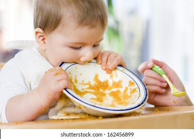 Hungry messy baby boy bitting the plate after eating vegetable puree.