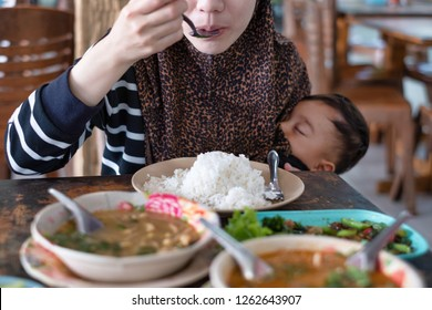 Hungry mother eating while baby sleep and breastfeeding