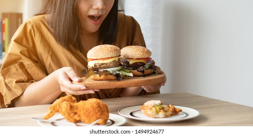 Hungry overweight woman holding hamburger on wooden plate, Fried chicken and Pizza on table .Concept of binge eating disorder (BED).