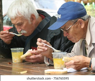 """Hungry people eat   hot soup with white bread during a """"kitchen for poor and elder people"""" before winter in Sofia, Bulgaria, Oct 9,2007. Public kitchen for Warm food for the poor people"""