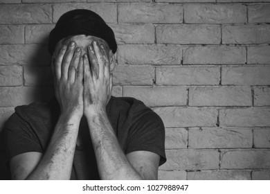Hungry poor man crying near brick wall