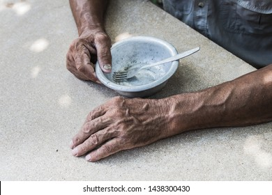 Hungry. Poor old man's hands an empty bowl. Selective focus. Poverty in retirement. Alms