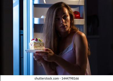 Hungry surprised woman in pajamas eating sweet cake at night near fridge. Stop diet and gain extra pounds because of high carbs food and unhealthy night eating