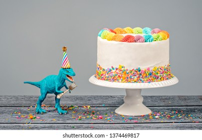 Hungry toy dinosaur wearing a hat and holding a fork next to a birthday Cake on a gray background