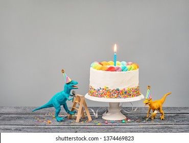 Hungry toy dinosaurs wearing hats and holding forks next to a birthday Cake on a gray background