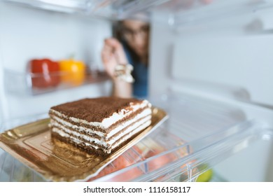 Hungry woman eating a dessert straight from the fridge using a fork, diet fail concept