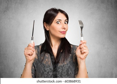 Hungry woman holding fork and knife