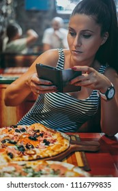 Hungry woman taking picture of her food in the restaurant