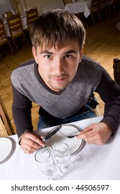 Hungry young man waiting for food in restaurant