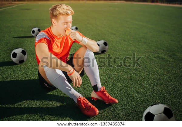Hungry young player sitting on lawn and eating apple. He has rest. Three balls are behind him. Fourth is in front. Sunny weather is outside.