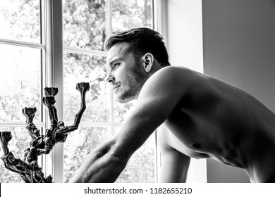 Hunky handsome shirtless man with pecs, abs and muscles looking out of window