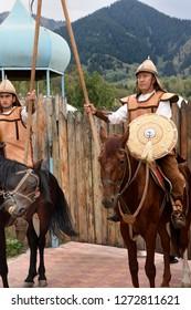 Huns Village, Talgar, Kazakhstan - September 2, 2016: Grinning horse photobombing two serious Hun guards with spear and shield Kazakhstan