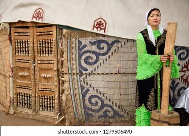 Huns Village, Talgar, Kazakhstan - September 2, 2016: Woman in traditional Kazakh dress grinding wool for felt next to a yurt at Huns village Kazakhstan