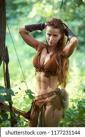 Hunt girl Amazon straightens her hair in the forest