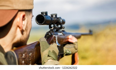 Hunter is aiming. Shooter sighting in the target. Hunter man. Hunting period. Male with a gun. Close up. Hunter with hunting gun and hunting form to hunt. The man is on the hunt. Hunt hunting rifle.