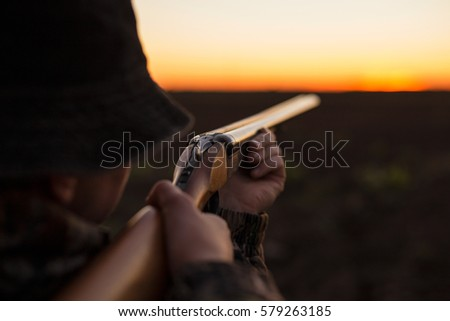 Hunter aiming shotgun in dusk