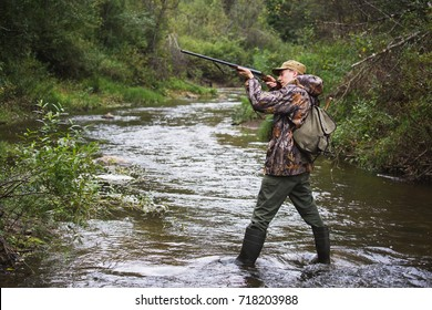 Hunter with a backpack and a hunting gun in the autumn forest. The man is on the hunt. The Hunter is aiming.
