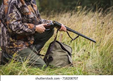 Caçador com uma mochila e uma arma de caça na floresta de outono. O homem está carregando um rifle de caça. Feche.