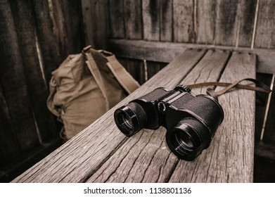Hunter binocular and backpack in the bench of wooden hunting box