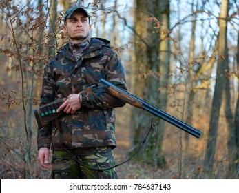 Hunter in camo suit with double barrel shotgun