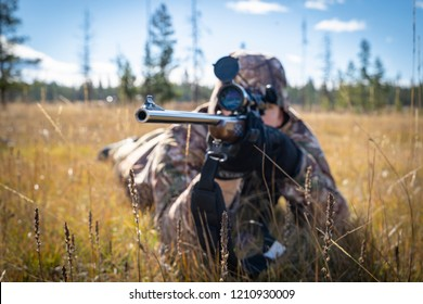 A Hunter In Camouflage Aiming a Scope and Rifle Close Up