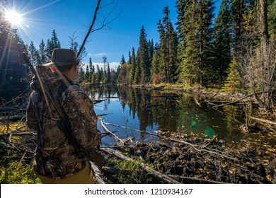 A Hunter in Camouflage Glassing Looking over a Small Pond in a Forest