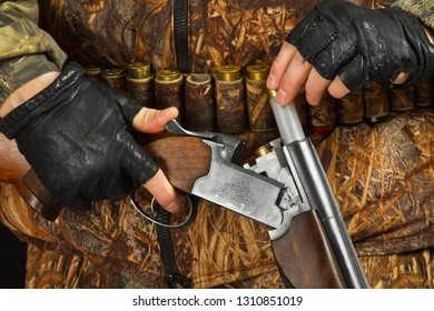 the hunter in camouflage makes charging a double-barreled shotgun, closeup