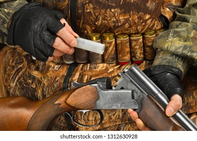 hunter in camouflage pulls out a shell casing from a shotgun, closeup