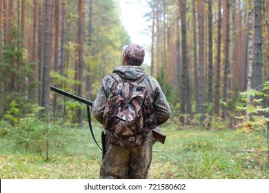 hunter in camouflage with shotgun walking in the forest