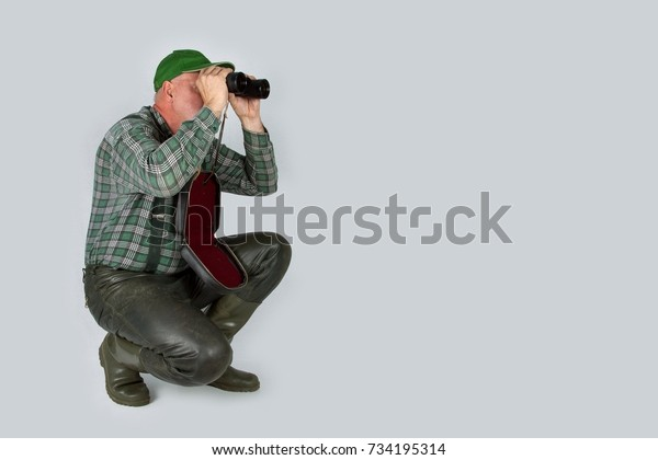 A hunter in the crouch looks through his binoculars in front of a white wall.