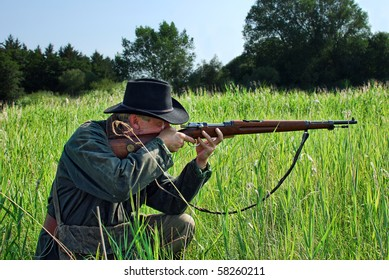 Hunter crouches in the grass and aims his rifle
