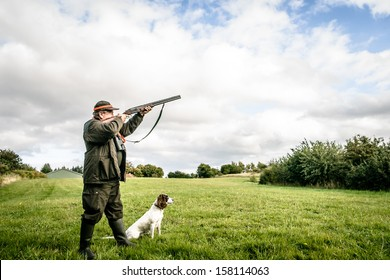 Hunter with dog aiming with his rifle