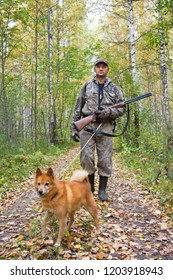 hunter with a dog on a leash walking on the forest road