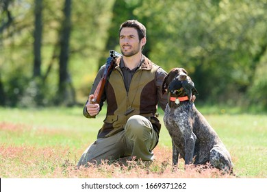 hunter with a dog in a pine forest