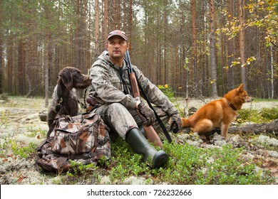 hunter with dogs during the rest on autumn hunting