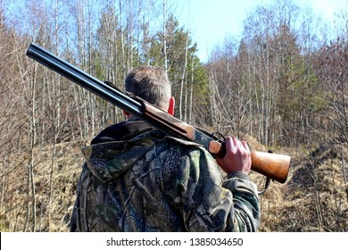 A hunter with a firearm on a spring hunting game.
