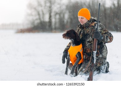hunter is fond of his dog. full length photo. copy space. friendship. owner looking at his pet with tender look