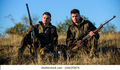 Hunter friend enjoy leisure in field. Hunting with friends hobby leisure. Hunters gamekeepers relaxing. Rest for real men concept. Discussing catch. Hunters with rifles relaxing in nature environment.