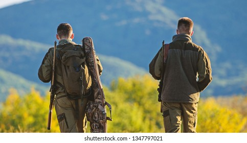 Hunter friend enjoy leisure. Hunters friends gamekeepers walk mountains background. Hunting with partner provide greater measure safety often fun and rewarding. Hunters rifles nature environment.