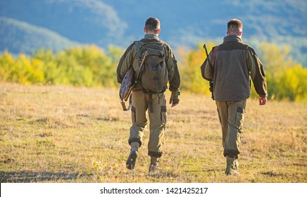 Hunter friend enjoy leisure. Hunting with partner provide greater measure safety often fun and rewarding. Hunters friends gamekeepers walk mountains background. Hunters rifles nature environment.