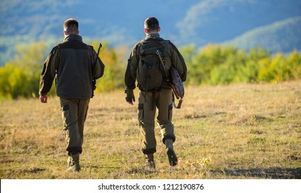 Hunter friends enjoy leisure. Hunting with partner provide greater measure safety often fun and rewarding. Hunters friends gamekeepers walk mountains background.