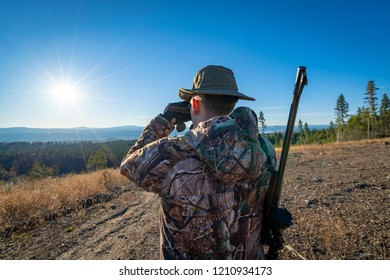 A Hunter Glassing with Binoculars at a Beautiful Landscape