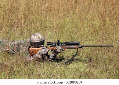 Hunter in grassy field with sniper rifle looking through scope at target