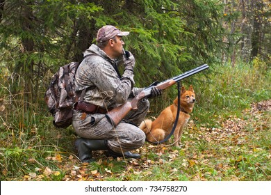 hunter with a grouse call waiting a prey